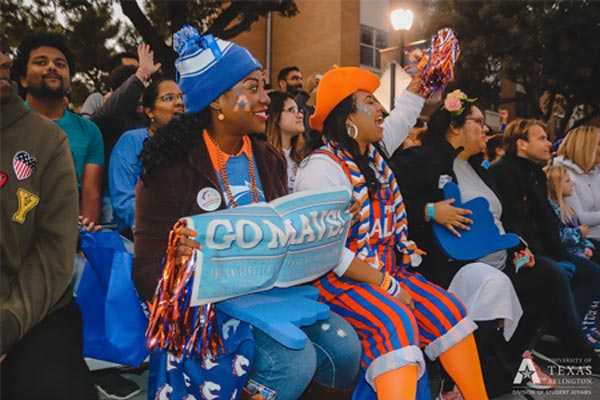 Two women dressed with spirit holding a 'GO MAVS!' sign and poms at Homecoming