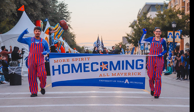 Two ambassadors in blue and orange stripes walking down the street with a sign between them labelled 'HOMECOMING'.