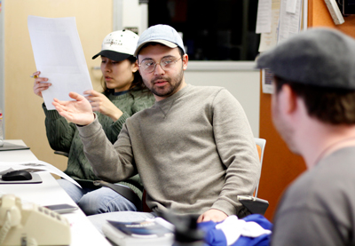 One woman reading a piece of paper while two men have a discussion