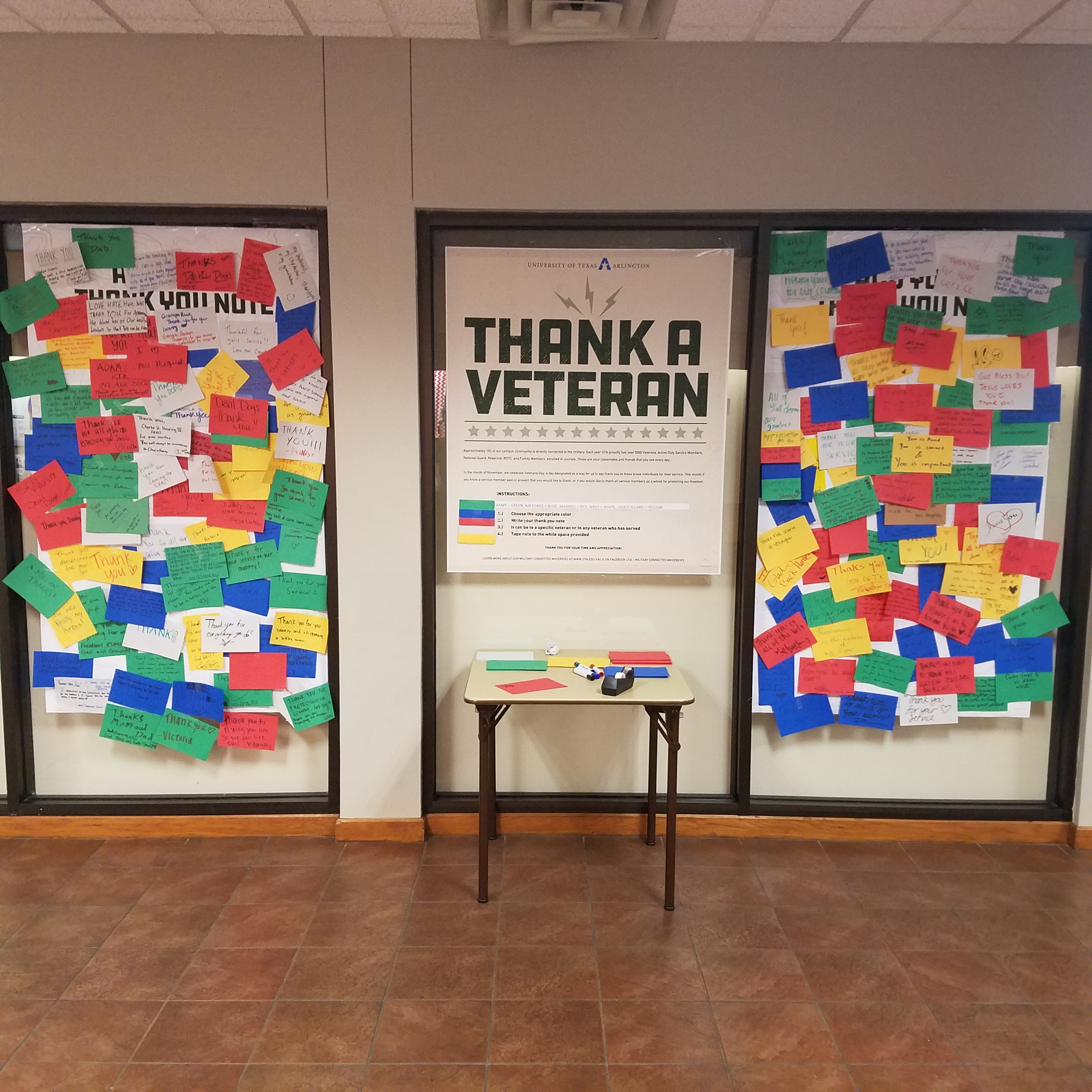 Bulletin boards with post it notes of many colors labeled 'thank a veteran'